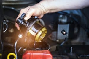 Car mechanic check the fuel filter at diesel engine. service or Preventive maintenance
